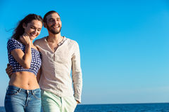 Couple walking on beach. Young happy interracial couple walking on beach. Royalty Free Stock Images