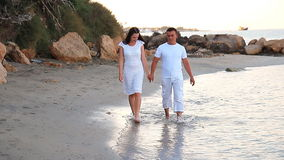 Couple walking on beach. Young happy interracial. Couple walking on beach smiling holding around each other. Asian woman, Caucasian man stock video