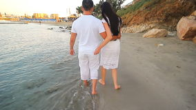 Couple walking on beach. Young happy interracial. Couple walking on beach smiling holding around each other. Asian woman, Caucasian man stock video footage