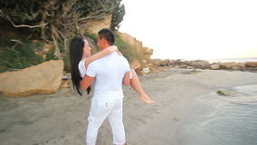 Couple walking on beach. Young happy interracial. Couple walking on beach smiling holding around each other. Asian woman, Caucasian man stock footage