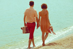 Couple walking on beach. Young happy married couple walking on beach holding around each other and holding their shoes. Sunny summer day. Outdoor shot Royalty Free Stock Image