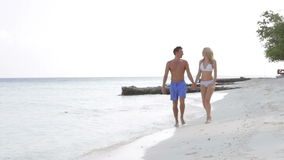 Couple Walking On Beautiful Beach. Camera tracks couple as they walk along beautiful beach looking happy.Shot on Canon 5d Mk2 with a frame rate of 30fps stock video