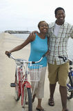 Couple Walking With Bicycles At Beach Royalty Free Stock Image