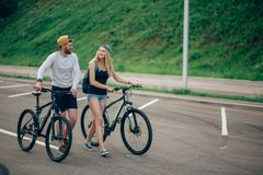 Couple Walking Bikes Together On Road To Stunning Sunset With Lens Flare Stock Images