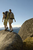 Couple Walking On Boulder At Coast Royalty Free Stock Image
