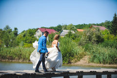 Couple Walking on Bridge with Champagne. Bride and groom with champagne walking on bridge Stock Photo