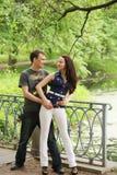 Couple walking on a bridge in a park. A couple walking on a bridge in a park Royalty Free Stock Images