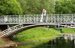 Couple walking on  bridge in park. A couple walking on a bridge in a park. Summer day Stock Photos