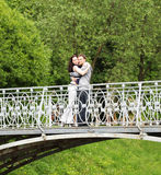 Couple walking on a bridge in park. A couple walking on a bridge in a park. Summer day Royalty Free Stock Image