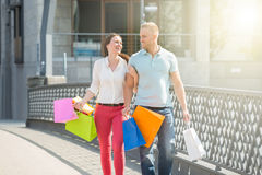 Couple Walking On Bridge With Shopping Bags. Young Happy Couple Walking On Bridge With Multi-colored Shopping Bags Royalty Free Stock Images