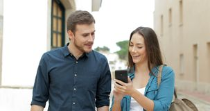 Couple walking browsing cellphone in the street. Happy couple walking towards camera browsing cellphone content in the street stock video footage