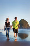 Couple walking on Cannon Beach. In Oregon, United states a popular tourist destination. background is Haystack rock in Cannon Beach royalty free stock photo