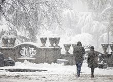 Couple walking by the city park in heavy snowfall royalty free stock photo