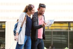 Couple walking in city with suitcases studying tourist map. Portrait of couple walking in city with suitcases studying tourist map Stock Photos