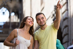 Couple walking through city. Young smiling travelers couple having city tour at vacation Stock Photo