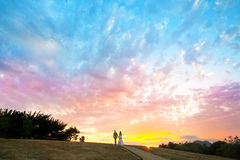 Couple walking into a colorful sunset Royalty Free Stock Image