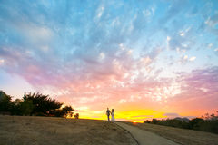 Couple walking into a colorful sunset Stock Photo