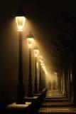 Couple walking on dark street illuminated with streetlamps Stock Photos