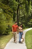 Couple walking dog. Stock Images