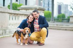 Couple walking with a dog in a city Royalty Free Stock Photography