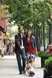 Couple Walking Dog On Sidewalk. Full length of a happy couple walking dog on sidewalk Royalty Free Stock Photography