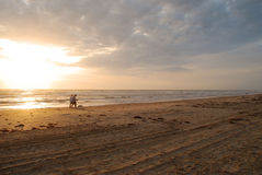 Couple walking the dog at sunrise. On the beach at South Padre Island, Texas stock photography
