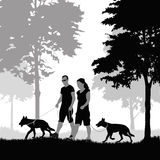 Couple walking with dogs Royalty Free Stock Photos