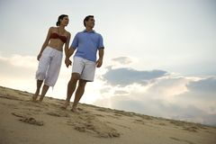 Couple walking down beach. royalty free stock photos