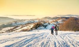 Couple walking down the snowy mountain in sunset time Stock Photo