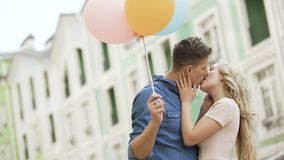 Couple walking down street, stopping to kiss, guy holding balloons, feelings. Stock footage stock footage