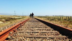 Couple walking down train tracks Royalty Free Stock Photos