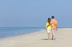 Couple Walking on An Empty Beach Stock Images