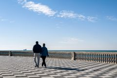 Couple walking on the famous Terrazza Mascagni in Livorno, Tuscany, Italy. Europe royalty free stock photography