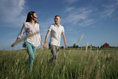 Couple walking through field Royalty Free Stock Image