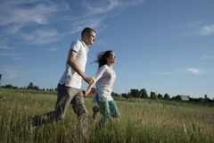Couple walking through field Royalty Free Stock Images