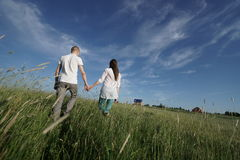 Couple walking through field Stock Photos