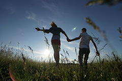 Couple walking through field. Young couple walking through green field Royalty Free Stock Photos