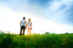 Couple walking through the field and holding hands Royalty Free Stock Photography