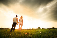 Couple walking through the field and holding hands Royalty Free Stock Images
