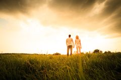Couple walking through the field and holding hands Royalty Free Stock Image