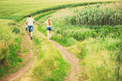 Couple walking in field Stock Photos