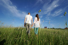 Couple walking through field Stock Photography