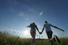 Couple walking through field Stock Photos