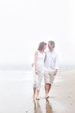Couple walking on a foggy beach smiling at each other Royalty Free Stock Images