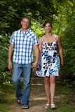 Couple Walking in forest. Happy smiling couple holding hands and walking in the forest Royalty Free Stock Photos