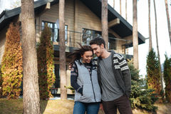 Couple walking in forest. Pretty young women and cheerful young men hugging and walking in forest near house Royalty Free Stock Photo