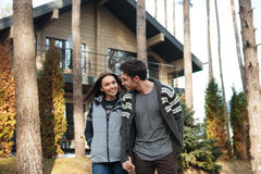 Couple walking in forest. Woman and cheerful young men hugging and walking in forest near house Stock Image