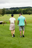 Couple walking on a golf course Stock Images