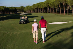 Couple walking on golf course Stock Images