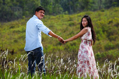 A Couple Walking Through A Grassland Royalty Free Stock Image
